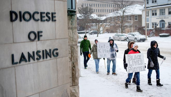 Protesters march in front of the Catholic Diocese of Lansing on Monday, Jan. 15, 2018, in downtown Lansing. More than 150 attended the protest in response to months of controversy surrounding kneeling protests at local Catholic Schools.Ê