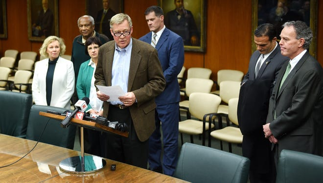 Michigan State University Board of Trustees Chairman Brian Breslin, center, reads a statement regarding MSU President Lou Anna K. Simon during a press conference on Friday, Jan. 19, 2018, in the Hannah Administration Building on the MSU campus in East Lansing. Standing by, from left, are fellow trustees Melanie Foster, Vice Chairman Joel Ferguson, Dianne Byrum, Mitch Lyons, Brian Mosallam and Dan Kelly.