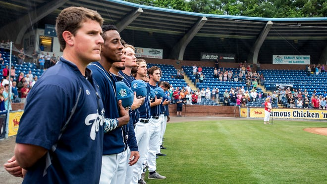 Asheville Tourists players holds their hats to their chests during the national anthem..