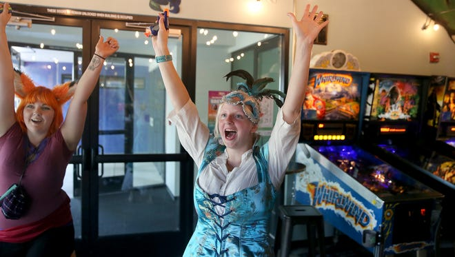Cynthia Gilman of Port Orchard, left, and Theresa Meigs of Bremerton celebrate during a game at Lovecraft Brewing on July 26, during the 2018 Nerd Crawl. During the event, often costumed participants played pinball and other games at a variety of downtown Bremerton bars, restaurants and arcades.