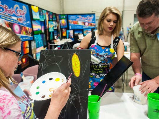 Sara Bielen, left, and Micah Berndt paint with Chuck Eve at the Brush Crazy booth during the What Women Want Expo Saturday, Oct. 10, 2015.