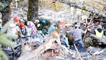 Workers at the site of the mudslide in Washington state.