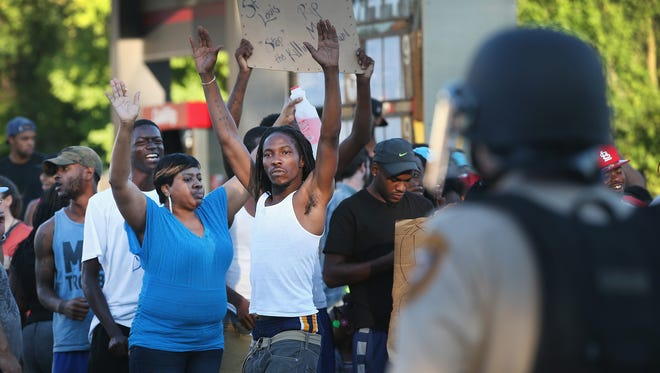 FERGUSON, MO - AUGUST 12:  Demonstrators protest the killing of teenager Michael Brown on August 12, 2014 in Ferguson, Missouri. Brown was shot and killed by a police officer on Saturday in the St. Louis suburb of Ferguson. Ferguson has experienced two days of violent protests since the killing but, tonight's protest was peaceful.  (Photo by Scott Olson/Getty Images) ORG XMIT: 506641261 ORIG FILE ID: 453548944