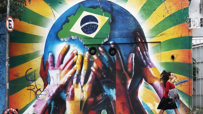 Graffiti of multi-colored hands supporting the planet marked with a Brazilian flag in Sao Paulo, Brazil.  The opening match for the 2014 FIFA World Cup is June 12 in Sao Paulo when Brazil takes on Croatia.