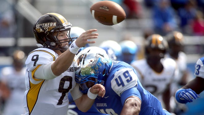 Southern Miss' quarterback Nick Mullens passes the ball as Middle Tennsessee's Steven Rhodes rushes in uring the first half of an NCAA college football game Saturday, Oct. 4, 2014, in Murfreesboro, Tenn. MTSU recovered the fumble. (AP Photo/Daily News Journal, Helen Comer)
