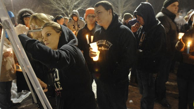 Before a candlelight remembrance vigil, Brittany Burns (left) on Jan. 18, 2014, signs a photograph of one of the victims of the Martin's Super Market shootings. Behind her is Justin Ratliff. The photographs were to be laminated and presented to the families.