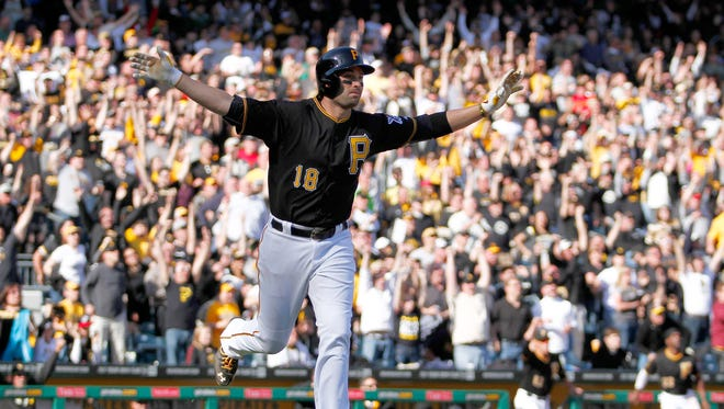 Neil Walker #18 of the Pittsburgh Pirates celebrates after hitting a walk off solo home run in the tenth inning against the Chicago Cubs during Opening Day at PNC Park March 31, 2014 in Pittsburgh, Pennsylvania.