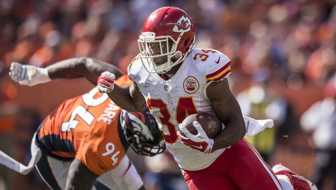 Kansas City Chiefs running back Knile Davis (34) scored on a two-yard rushing touchdown in the second quarter, running past Denver Broncos defensive end DeMarcus Ware (94) on September 14, 2014 at Sports Authority Field at Mile High in Denver. The Chiefs lost 24-17. (