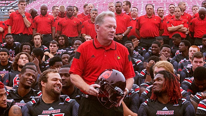 UofL offensive guard Jake Smith, left, and defensive end Lorenzo Mauldin, right, flank UofL Head Football Coach Bobby Petrino as the team poses for its photo on media day at Papa John's Cardinal Stadium. 09 August 2014