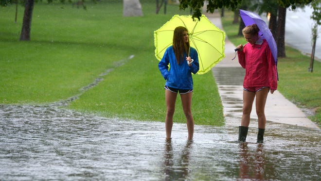 Hadley Mills, left, and Sofia Springer check out flooding in Boulder, Colo., on Wednesday, July 30, 2014. (AP Photo/The Daily Camera, Paul Aiken)