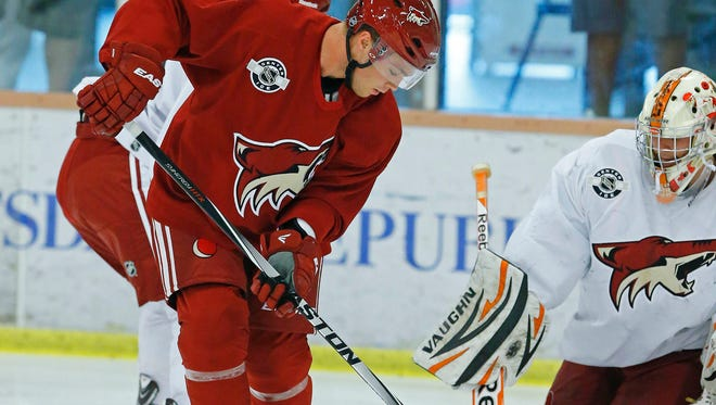 Max Domi of the Coyotes eyes the puck in front of goalie Marek Langhamer during prospect-development camp on Tuesday at the Ice Den in Scottsdale.