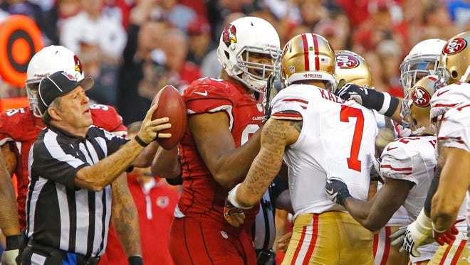 Cardinals defensive end Calais Campbell (93) holds back San Francisco 49ers quarterback Colin Kaepernick (7) after a scuffle in their NFL football game Sunday, Dec. 29, 2013 in Glendale.