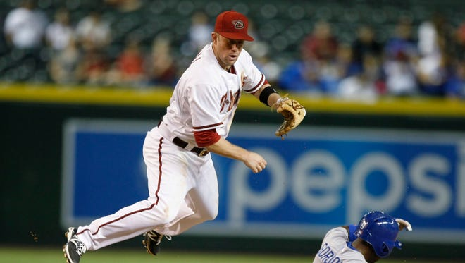 Arizona Diamondbacks second baseman Aaron Hill turns the double play while avoiding Los Angeles Dodgers' Dee Gordon  in the eighth inning, Aug. 26, 2014, in Phoenix.