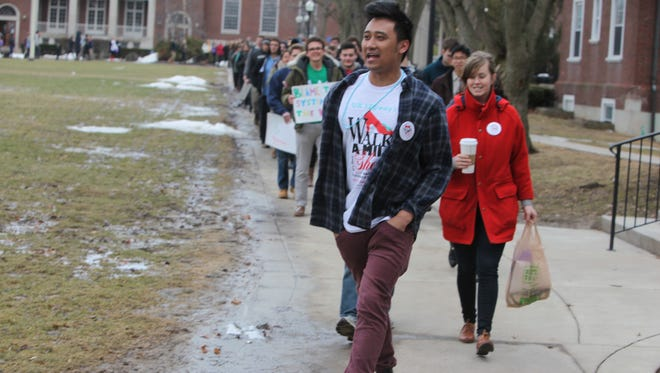 Sevi Poblete, left, leads a trail of students on a mile-long walk Saturday for the first Walk a Mile in Her Shoes event at the University of Rochester.