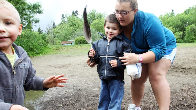 Jake Linville, 4, shows off a newly found feather, while Taylor Pace, also 4 tries to get in the photograph. Cook Park in Tigard stretches along the Tualatin River, home to ducks, robins, squirrels and all manner of forest-dwellers in addition to the the insects of the Tupling Butterfly Garden.