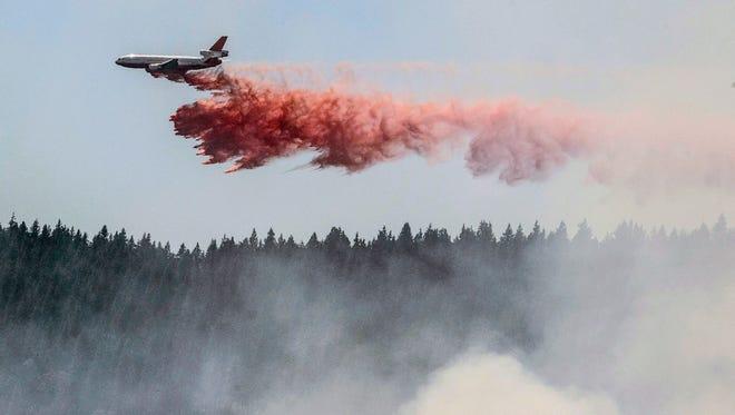 A plane drops fire retardant as firefighters battle a blaze in El Portal, Calif.