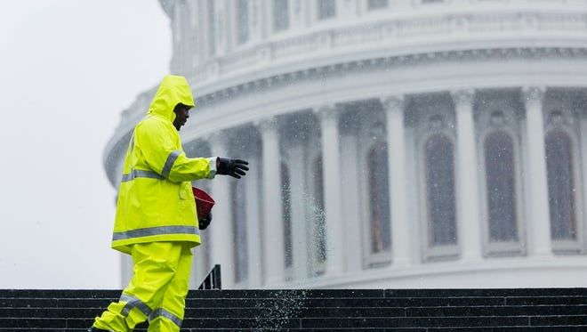 A worker salts the steps outside the U.S. Capitol on Tuesday.