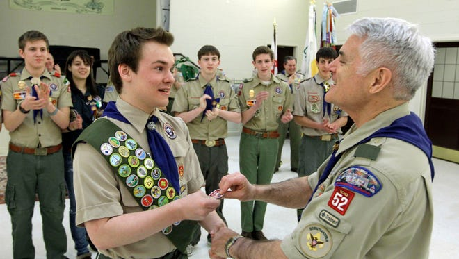 Pascal Tessier, left, a gay Boy Scout, receives his Eagle Scout badge from Troop 52 Scoutmaster Don Beckham, right, in Chevy Chase, Md., to become one of the first openly gay scouts to reach scouting's highest rank.