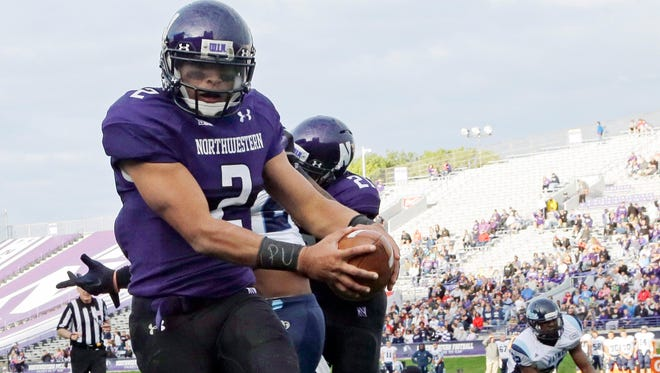 """Northwestern quarterback Kain Colter (2) wears APU for """"All Players United"""" on his wrist tape last year in Evanston, Ill."""