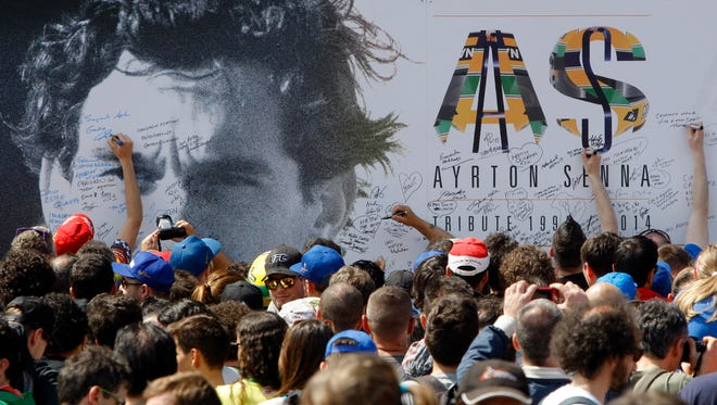 People sign a board with an image of Ayrton Senna during a memorial Thursday at the Imola race track where he died in a crash 20 years ago.