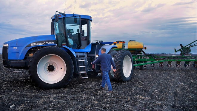 Central Illinois corn and soybean farmer Michael Mahoney walks back to his tractor to continue planting seed corn into the evening in Ashland, Ill.