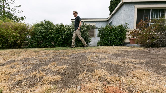 Michael Korte walks on his home brown lawn in Glendora, Calif., outside of Los Angeles, on July 17.