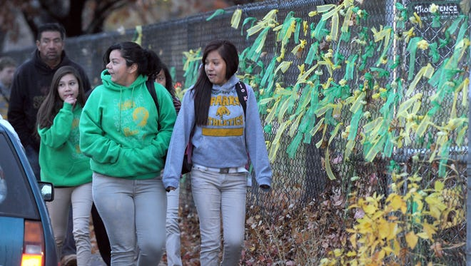 Sparks Middle School students walk past a fence with ribbons and flowers left as a memorial to slain teacher Michael Landsberry on Oct. 28,  2013, the first day of school since  the school shooting a week ago.