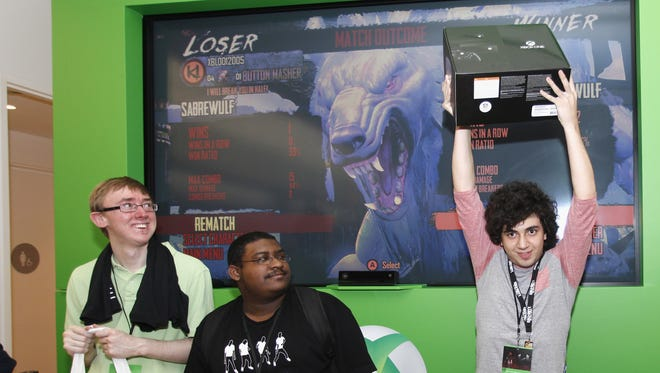 Zainalbidin Abdulwahab, right, holds up his Xbox One which he won after competing in a gaming tournament at a Microsoft retail store in Houston.