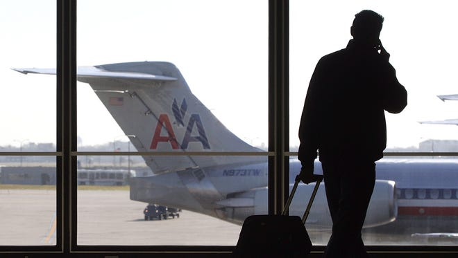 A traveler talks on his cell phone as he walks past a parked American Airlines jet awaiting its departure.