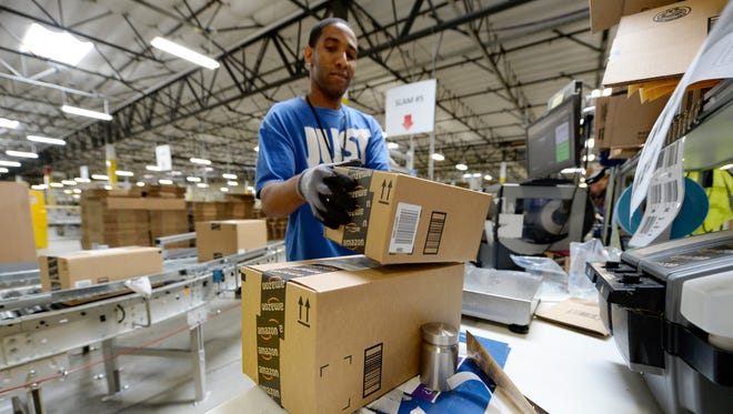 Employee Lamar Roby prepares shipping orders at Amazon's San Bernardino Fulfillment Center Oct. 29, 2013 in San Bernardino, Calif.