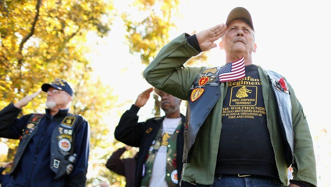 Vietnam War veteran Jim Hauser of Riva, Md., salutes with fellow veterans during a Veterans Day event at the Vietnam Veterans Memorial on the National Mall on Nov. 11 in Washington.