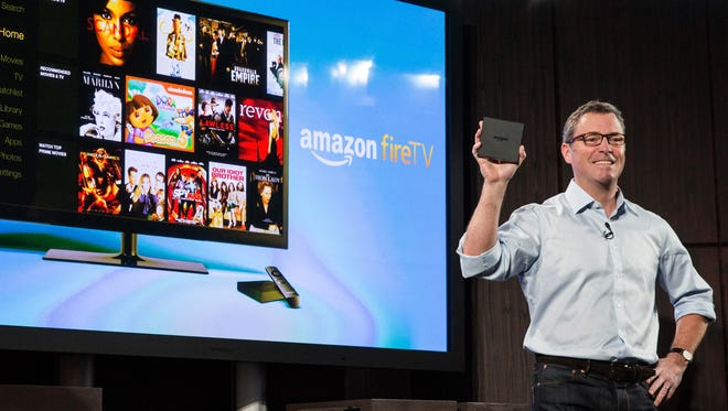 Amazon's vice president of Kindle, Peter Larsen, displays the Amazon Fire TV, a new device that allows users to stream video, music, photos, games and more through their television, on April 2, 2014 in New York City.