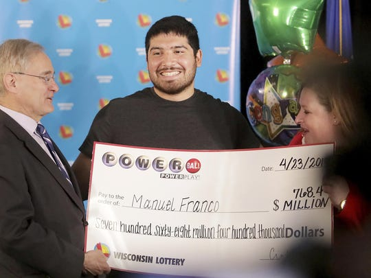 Manuel Franco of West Allis, Wis., winner of second-highest Powerball lottery in history, attends a news conference at the Wisconsin Department of Revenue in Madison, Wis., on Tuesday, April 23, 2019. At right is Peter Barca, state secretary of revenue, and at right is Cindy Polzin, state lottery director.