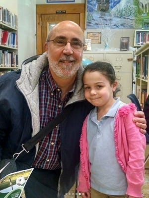 Pastor Frank Marchiano of Faith Bible Church in Vineland visits Madison, an elementary student, in the library at Cumberland Christian School.