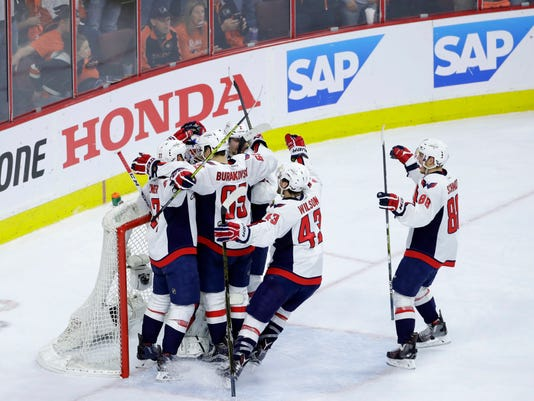 Washington Capitals' players celebrate with goalie Braden Holtby after winning Game 6 against the Philadelphia Flyers in the first round of the NHL Stanley Cup hockey playoffs, Sunday, April 24, 2016, in Philadelphia. (AP Photo/Matt Slocum)