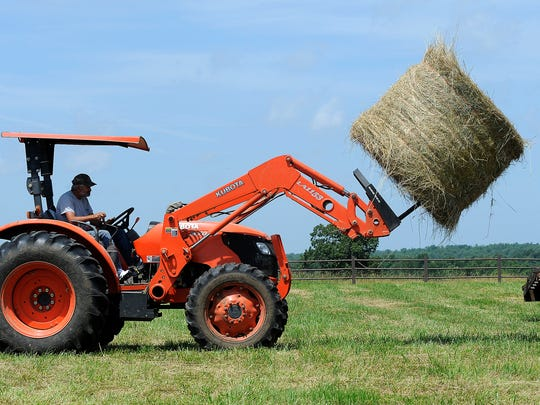 Rick Cowart moves hay bales at the Marilyn Sierling cattle ranch in the Ozark Mountains near Midway, Arkansas.