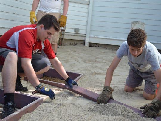 James DeVanna, left, grades  the foundation for a patio