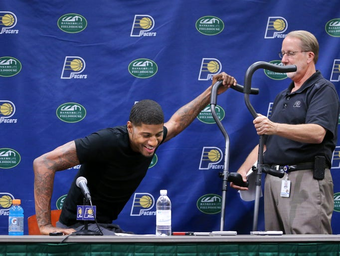 Indiana Pacers forward Paul George gets help from David Benner, Director of Media Relations with the Pacers, with his crutches after fielding questions from the media about his accident, recovery and his future with the Pacers during a press conference held at Bankers Life Fieldhouse on Friday, August 15, 2014.