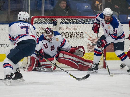 U.S. NTDP U18s goalie Drew DeRidder looks through traffic against Ferris State. Helping out are Trevor Janicke (7) and Spencer Stastney (25).