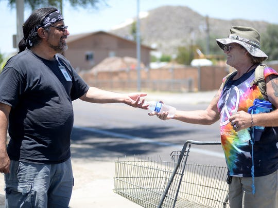 David Palladini, family services case worker, hands a couple of water bottles to Charley Scaff as he walks past on his way to the nearby food bank on Thursday, June 18, 2015.