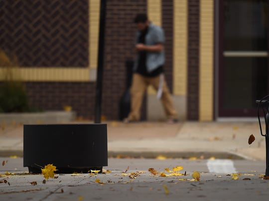 Leaves blow across the sidewalk Thursday as a pedestrian makes his way along North Washington Street in downtown Green Bay.