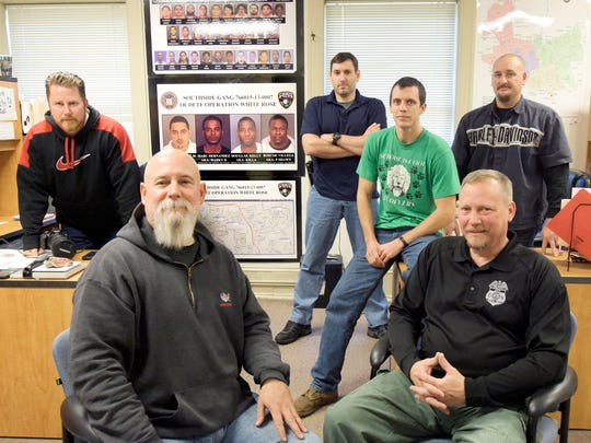 York City Narcotics Squad and Nuisance Abatement officers, from left, Detective Scott Nadzom, Detective First Class Andy Shaffer, Officer Stephen Aderhold, Officer Zach Pelton, ATF Special Agent Scott Endy and Detective Bart Seelig, pose in their headquarters in an old York City fire station. The poster on the wall references the city's Southside gang, whose members are serving lengthy federal sentences due to the efforts of the group. (Bill Kalina - The York Dispatch)