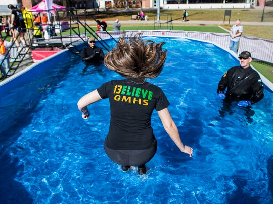 Alison Treglia jumps into a swimming pool during the UD Polar Plunge on the campus at the University of Delaware on Sunday afternoon.
