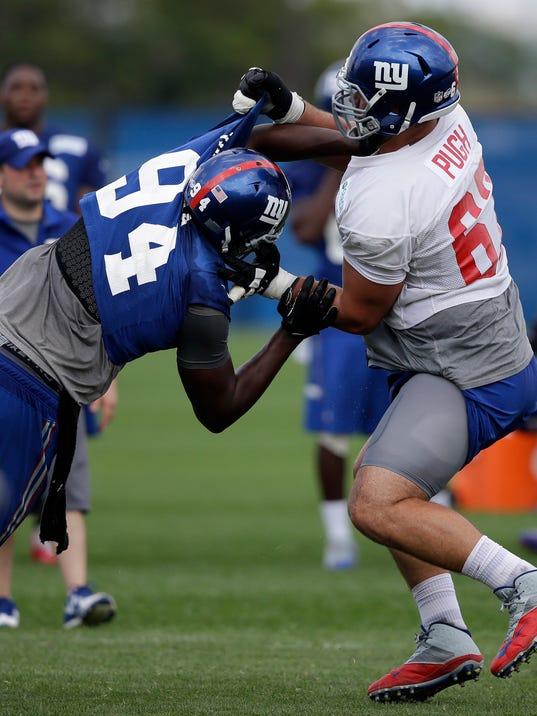 New York Giants' Justin Pugh, right, blocks and Mathias Kiwanuka during NFL football training camp in East Rutherford, N.J., Tuesday, July 22, 2014. (AP Photo/Seth Wenig)
