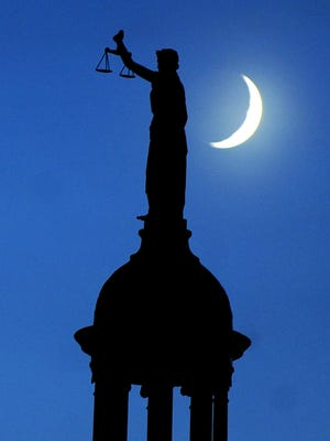 Mike Tripp/The News Leader From its place atop the Augusta County courthouse, the statue of Lady Justice stands silhouetted against the evening sky as the crescent moon drops lower in the western skies over Staunton on Wednesday, Oct. 21, 2009.  Originally designed by architect T.J. Collins, the building that currently serves as the county's courthouse became the fifth to occupy that location in 1901. Built in 1745, the original was a crude log structure. The next full moon occurs Monday, Nov. 2.