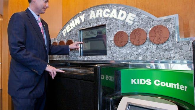 Jim Kiernan, Shore market president at TD Bank in Tinton Falls, at the coin-counting machine in the bank.