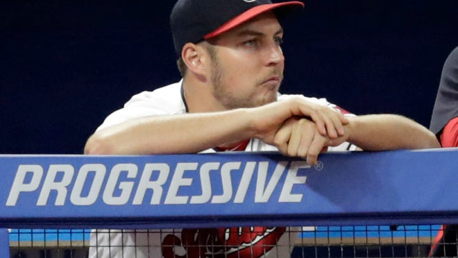 FILE - In this July 10, 2018, file photo, Cleveland Indians pitcher Trevor Bauer watches from the dugout during the ninth inning of a baseball game against the Cincinnati Reds in Cleveland. Bauer threw off the mound this week as he continues to recover from a stress fracture in his right leg. He is hoping to be back in time to help the Indians in the postseason. (AP Photo/Tony Dejak, File)