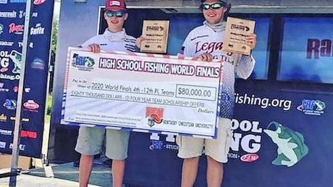 From left, Lenexa's Ryder Mains and Mason Chapman pose with a giant check denoting their $80,000 scholarship offers to Kentucky Christian University after finishing 12th at the FLW World Finals on Saturday on the Mississippi River at Lacrosse, Wis.