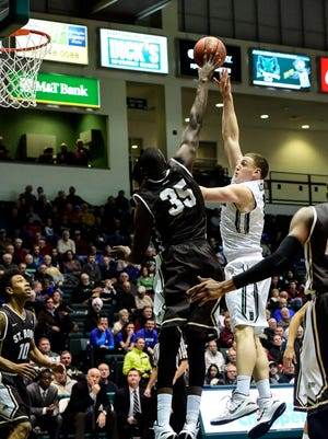 Binghamton University's Bobby Ahearn makes a basket while being covered by St. Bonaventure's Youssou Ndoye during a game in the Events Center in December 2014.