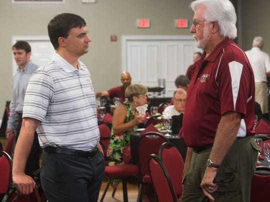 Troy University's head football coach, Neal Brown, left talks with former Troy athlete and supporter Wayland Foster, right, during a luncheon at New World Landing Thursday.
